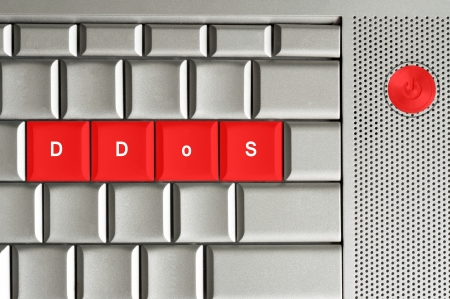 scamming: distributed denial of service in red on a metallic keyboard Stock Photo