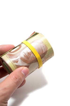 fifty dollar bill: Hand holding a roll of 50 dollars Canadian with yellow plastic band over the eyes  Stock Photo