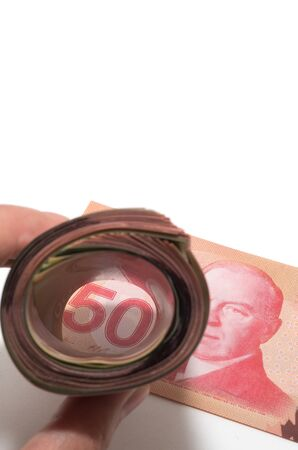 A roll of bank notes focusing on a 50 Canadian dollars photo