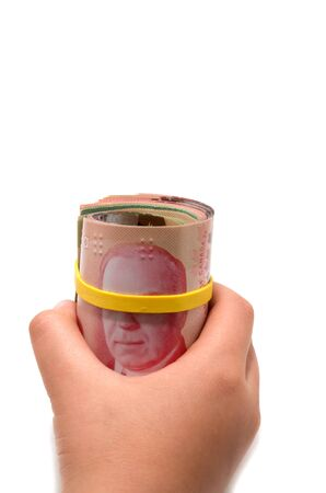 Hand holding a roll of 50 dollars Canadian with yellow plastic band over the eyes  photo