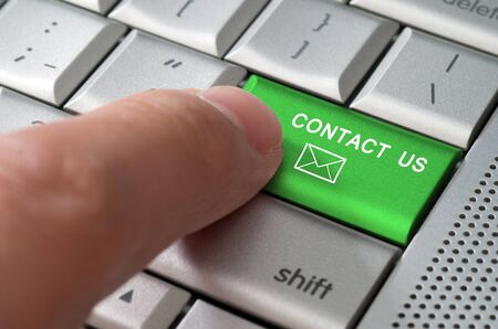 contact info: Business concept male finger pointing contact us key on metallic keyboard