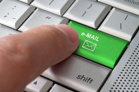 Business concept male finger pointing e-mail key on a metallic keyboard photo
