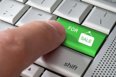 Business concept male finger pointing for sale key on  a metallic keyboard photo