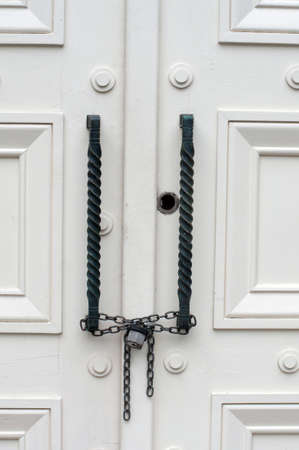 Locked and chained white wooden doors photo