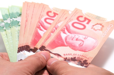 Hand holding a series of Canadian banknotes on white background Stock Photo