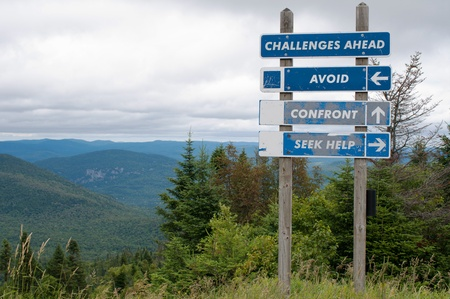 Signpost on top of the mountain warning challenges ahead and three options photo