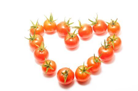 Cherry tomatoes heart shape on white background photo