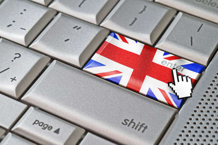 Business concept mouse cursor pressing United Kingdom enter key on metallic keyboard photo