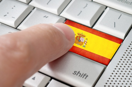 spaniards: Business concept male finger pressing Spain enter key on metallic keyboard