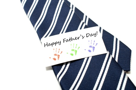 Happy Father s Day with colorful hand prints tag on blue tie over white background photo