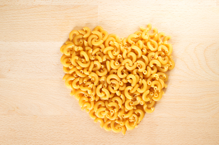 Macaroni forming a heart over a wooden cut board. Concept of healthy food.  版權商用圖片