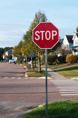 Stop sign at street corner with pedestrian cross path photo