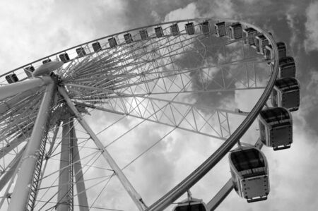 Large ferris wheel against clear blue sky in black and white
