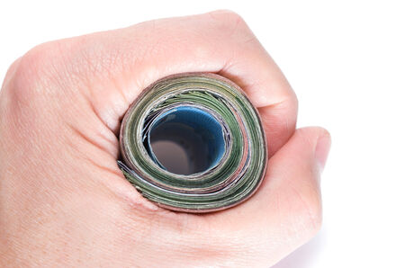 Asian Hand holding firmly a roll of bank notes on white background Stock Photo - 24984611