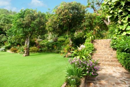 여름 기간 동안 계단 집 정원에서 자연적인 돌 조경 스톡 콘텐츠