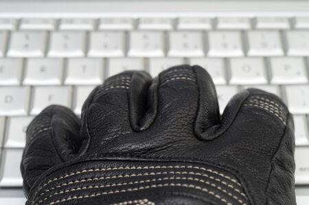 spammer: Hacking concept with hand in black leather glove over the laptop keyboard Stock Photo