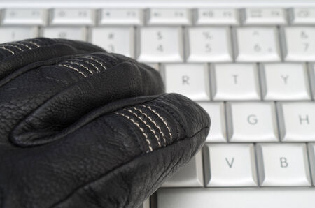 Hacking concept with hand in black leather glove over the laptop keyboard photo