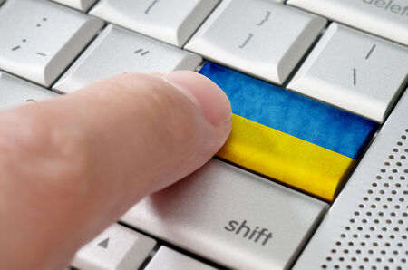 electronic commerce: Business concept male finger pressing Ukraine enter key on metallic keyboard