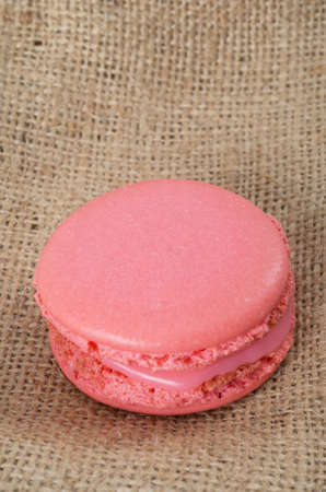 Homemade Pink macaroon on brown  fabric background photo