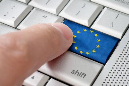 europe: Business concept male finger pressing Union European enter key on metallic keyboard