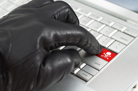scamming: Hacker concept with hand wearing black leather glove pressing enter key button on a metallic laptop keyboard