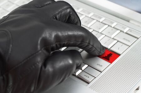 spy ware: Online spy ware concept with hand wearing black leather glove pressing enter key on metallic laptop keyboard
