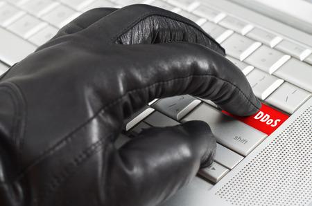 pirated: hand wearing black leather glove pressing enter key on metallic laptop keyboard Stock Photo