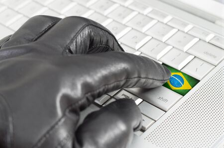leather glove: Hacking Brazil concept with hand wearing black leather glove pressing enter key with flag overlaid