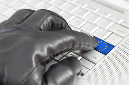 leather glove: Hacking Europe concept with hand wearing black leather glove pressing enter key with flag overlaid