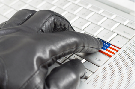 leather glove: Hacking USA concept with hand wearing black leather glove pressing enter key with flag overlaid Stock Photo