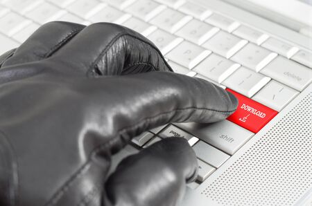 scamming: Online illegal download with hand wearing black leather glove pressing enter key Stock Photo