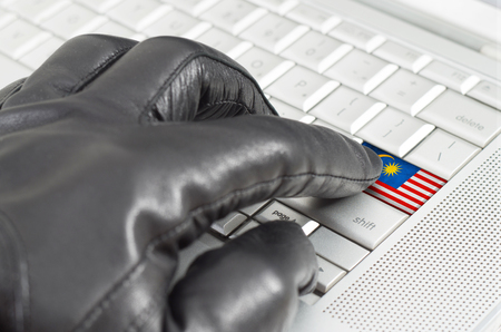 scamming: Hacking Malaysia concept with hand wearing black leather glove pressing enter key with flag overlaid
