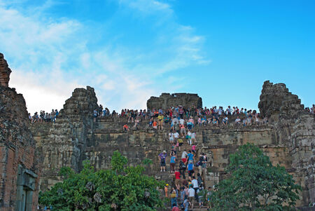Siem Reap , CAMBODIA - MAY 02: Unidentified tourists climbing to the top of a tower at Angkor Wat to watch sunset.