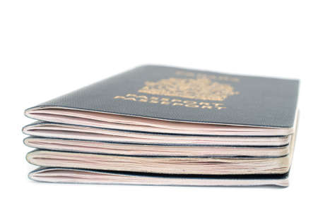 Pile of five passports viewed from the side on white bacground photo