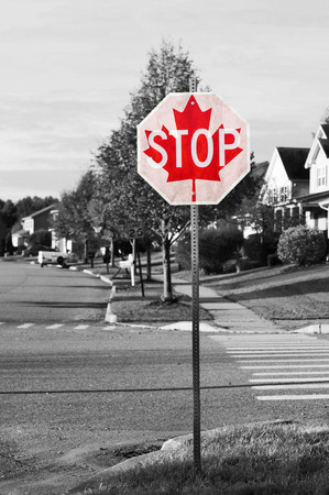 Canadian stop sign concept on black and white street scene with selective color on the stop sign photo