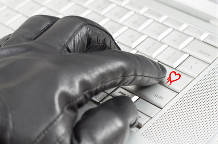 scamming: Online exploiting heartbleed bug concept with hand wearing black glove  Stock Photo