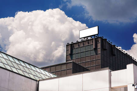Blank advertising billboard sign on top of a building against blue sky with clouds photo