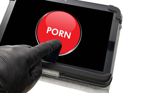 scamming: On-line mobile pornography concept with hand wearing black glove pointing a touch screen