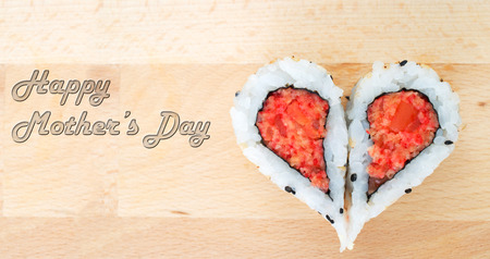 Happy Mothers Day concept with sushis forming a heartp shape on wooden cutting board photo