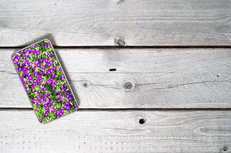 Modern mobile device showing violet flowers on top of an old wooden table Stock Photo - 32169263
