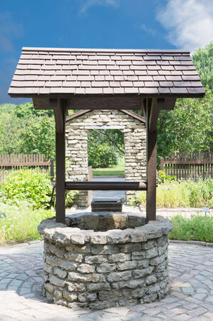 well made: Old wishing well made of little stones against nice green landscape