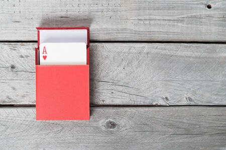 Playing cards in a red box on wooden background photo