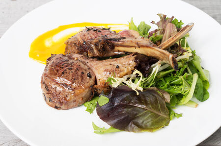 Grilled lamb chops on a bed of vegetables photo