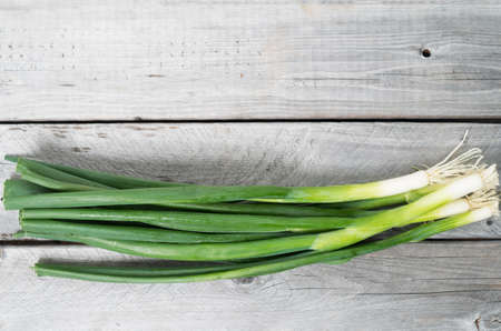 Bunch of spring onions against wooden background photo