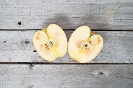 two and a half: Spoiled apple cut in two half on wooden background Stock Photo