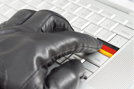 scamming: Hacking Germany concept with hand wearing black leather glove pressing enter key with flag overlaid