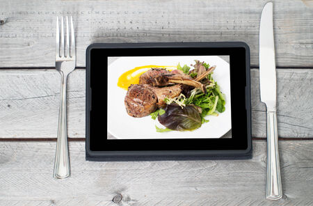Online ordering food concept with table setting and meal course on a tablet screen Фото со стока - 34012381