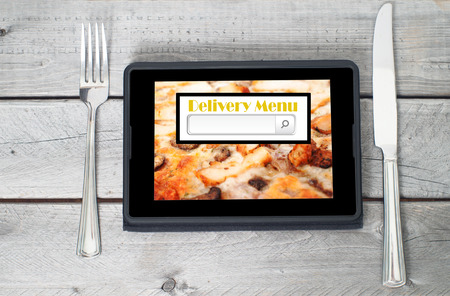 On-line and Internet food delivery concept with a digital tablet Banque d'images