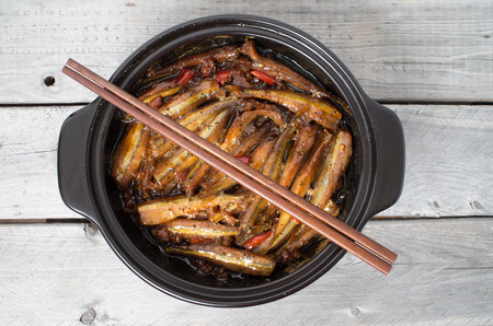 Vietnamese caramelized smelt fishes in clay pot on a wooden table - Ca Kho To Stock Photo