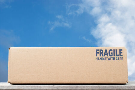 handle with care: Shipping box with fragile handle with care as notice against blue sky background Stock Photo